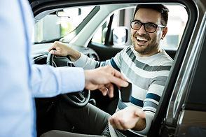 young-happy-man-receiving-new-car-keys-i
