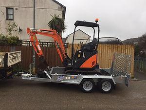 orange and black mini digger and silver trailer