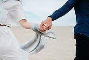 Couple d'amoureux qui se tient par la main à la plage