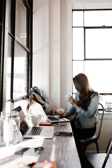 Femme qui boit un café devant son ordina