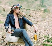 Jeune marié boho assis en forêt avec un verre à la main