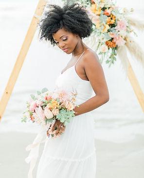 Jeune mariée à la plage avec bouquet de