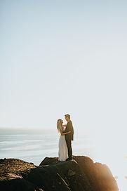 Couple de mariés qui s'embrasse debout sur une falaise