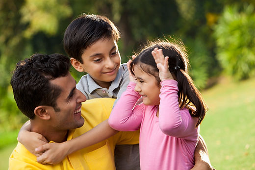 Stock photo of a Latino man being hugged by his son while smiling at his daugter holding her hands up to her temples to make a silly face.