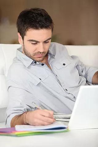 man writing behind laptop