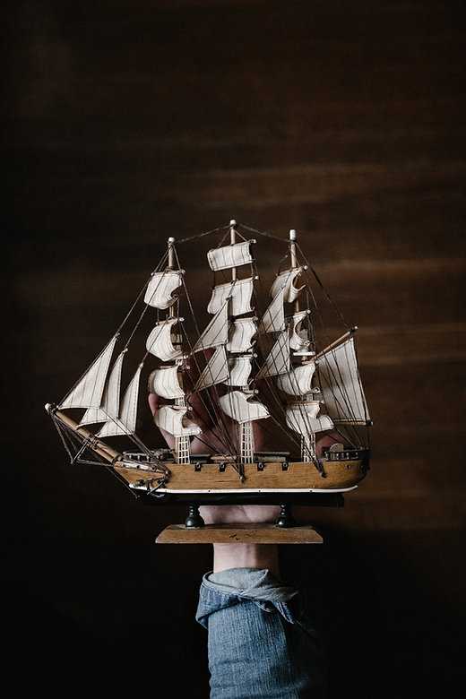 Person holding a vintage model ship