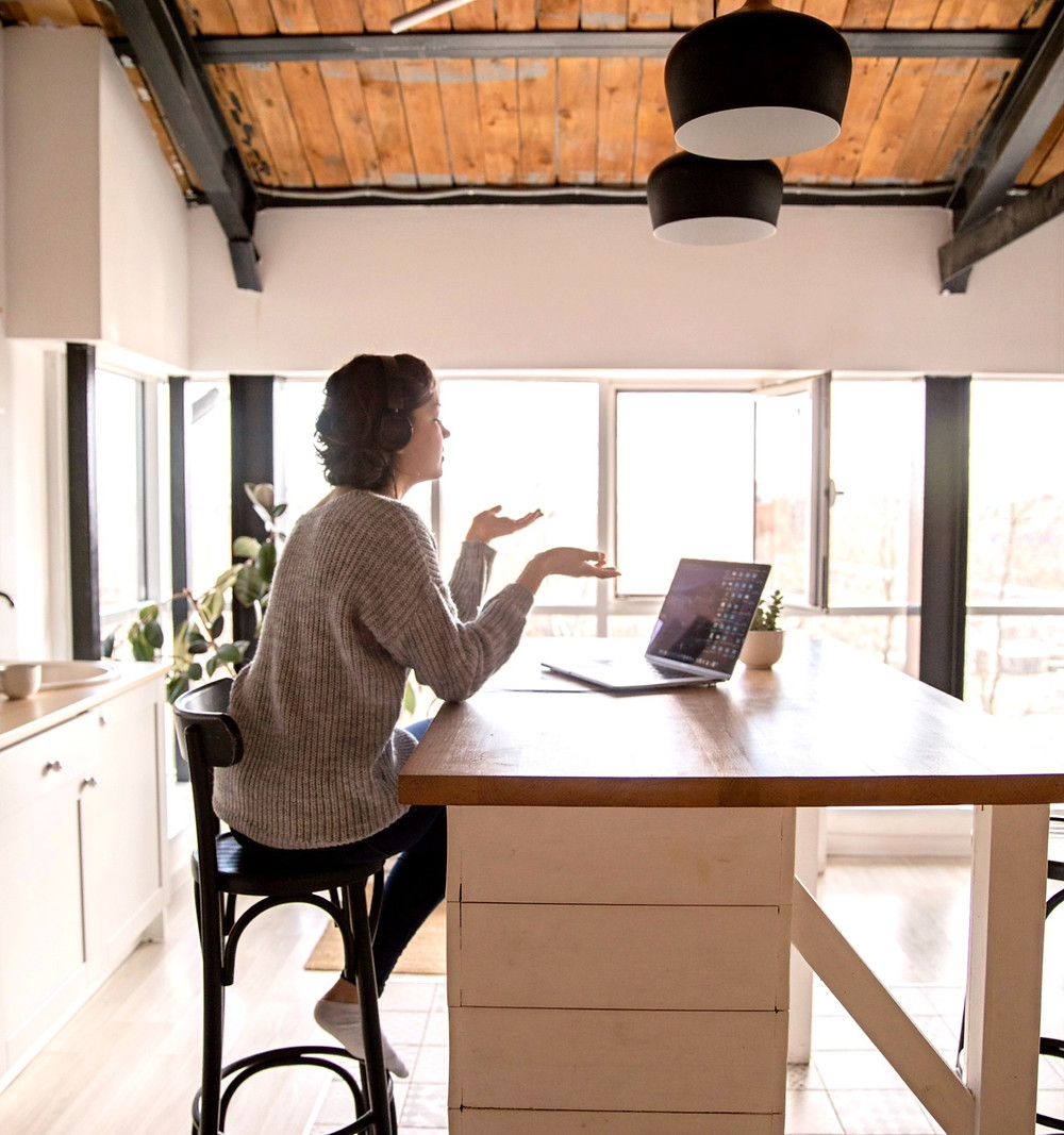 Woman working from home, conducting business from laptop in kitchen during quarantine due to COVID19