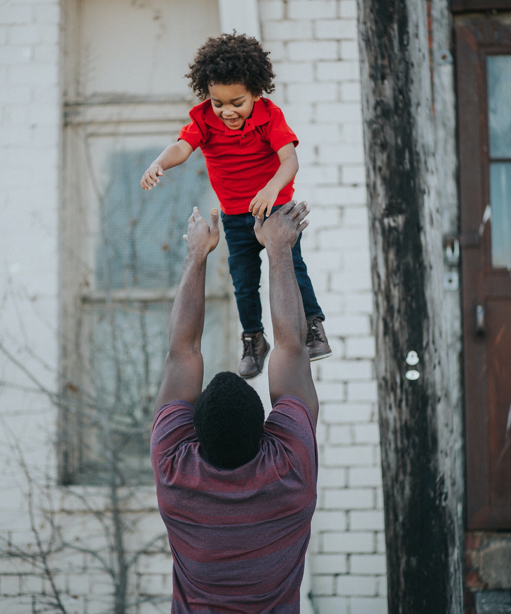 Dad throwing toddler boy in the air to catch; child smiling.