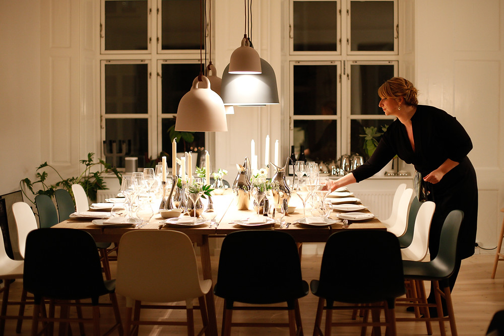 A lady lighting candles and preparing a large dining room table for many guest.