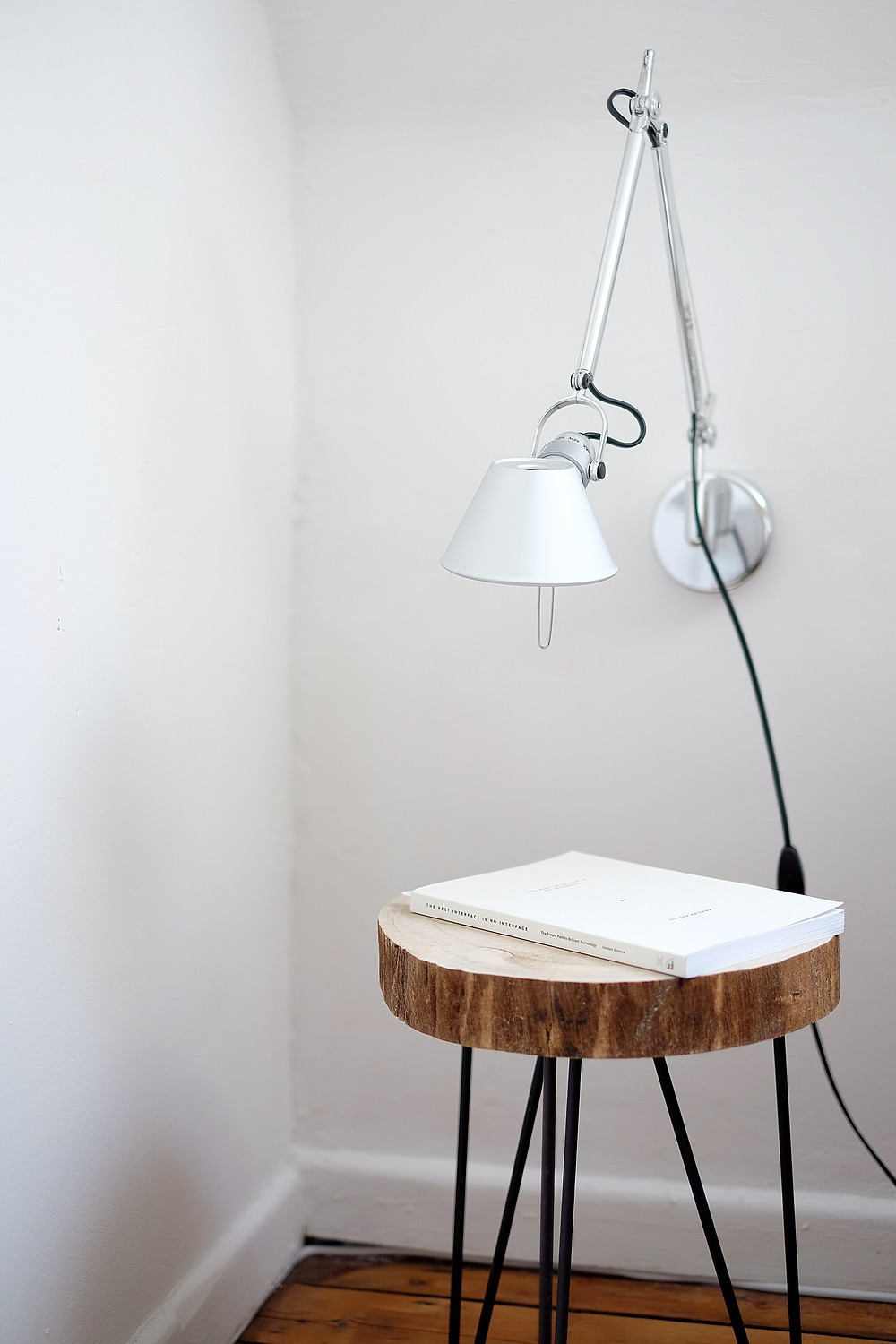 Simple modern rustic wood log side table with a white book placed on top and a clean wall reading lamp. White space suggests minimal modern design.