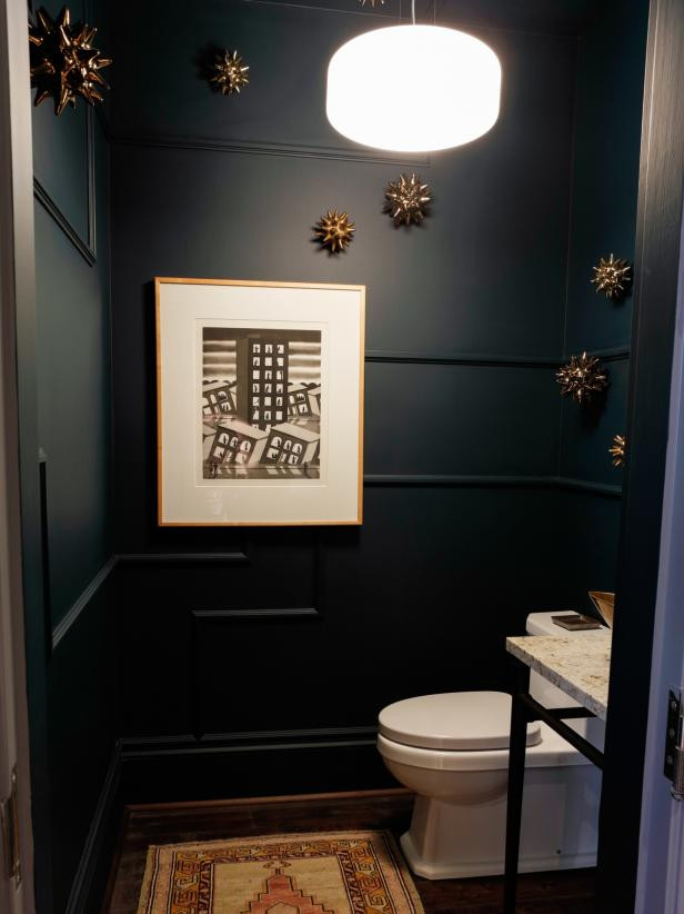 Dark and moody blue green powder room with modern details.