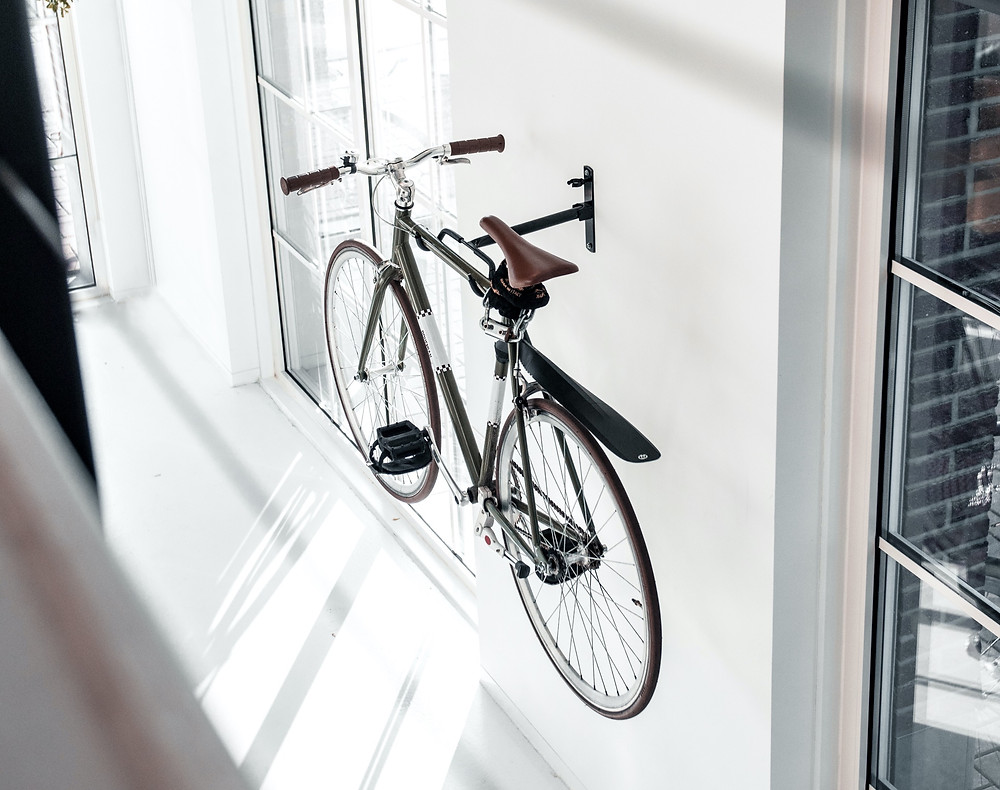 Modern clean white apartment with nice bike hung on wall.