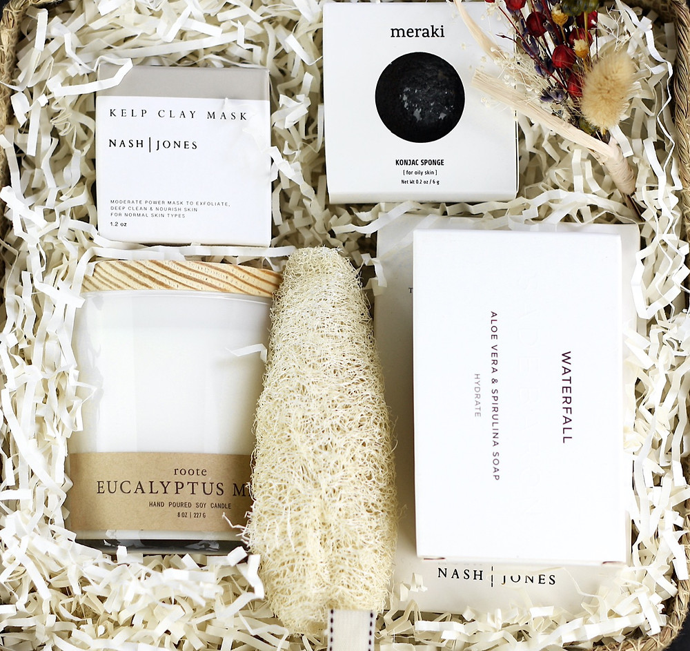 A beautiful neutral-colored spa gift basket with high-end clean bath and body products.