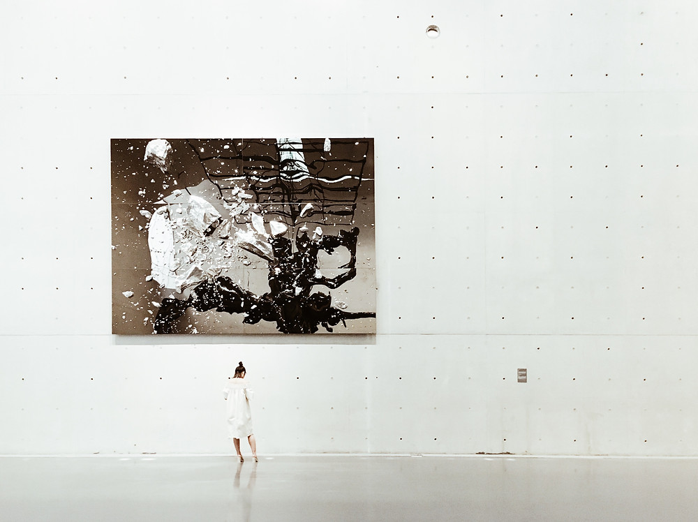 Large abstract monochromatic painting on a large white industrial wall with woman dwarfed by art wearing a white dress.