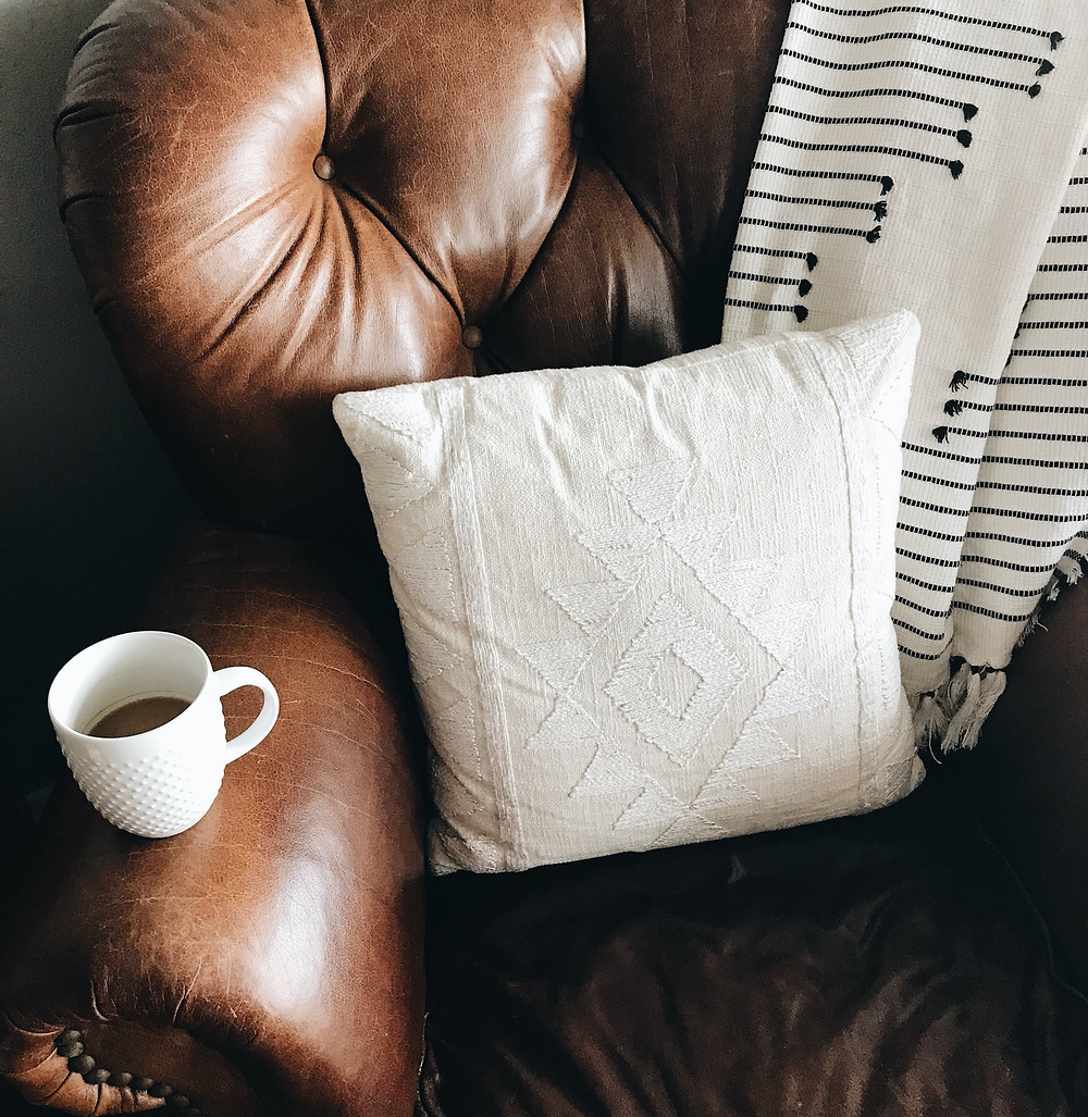Soft worn leather sofa with coffee cup and soft throw. Perfect spot to curl up and read a book.