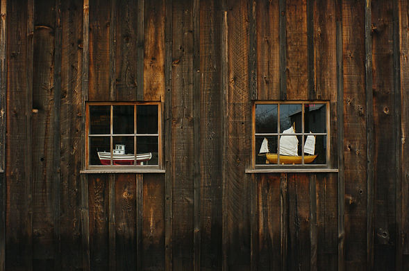 old wood shed near ocean with model boats in window