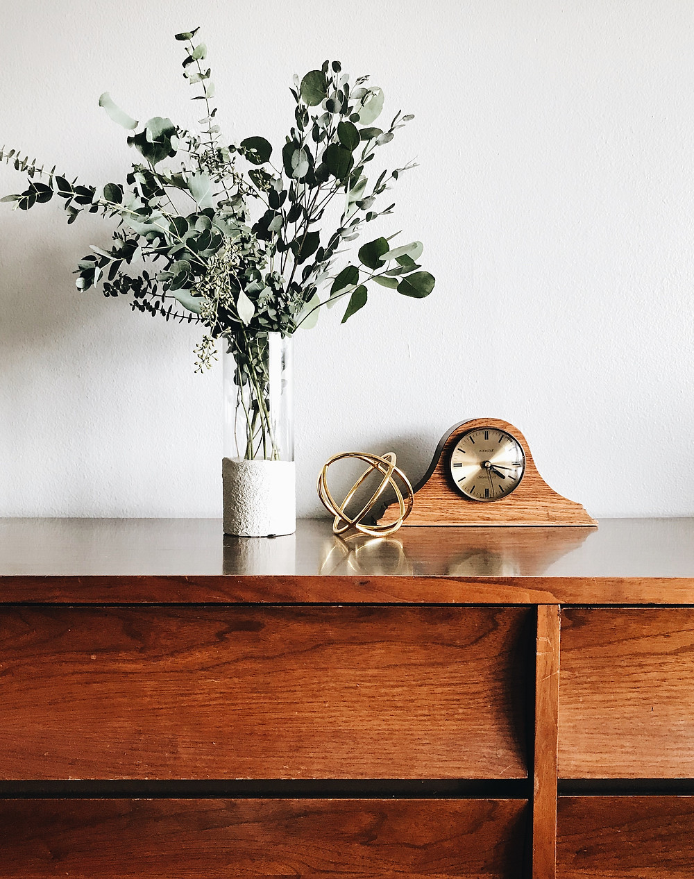 Vintage min-century furniture with modern vase and eucalyptus branches.