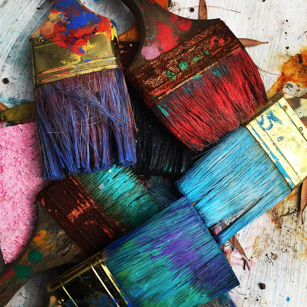 A pile of worn paint brushes with various wild and bold colors of paint.
