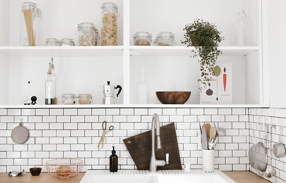 Clean modern open shelving in kitchen with white subway tile backsplash.