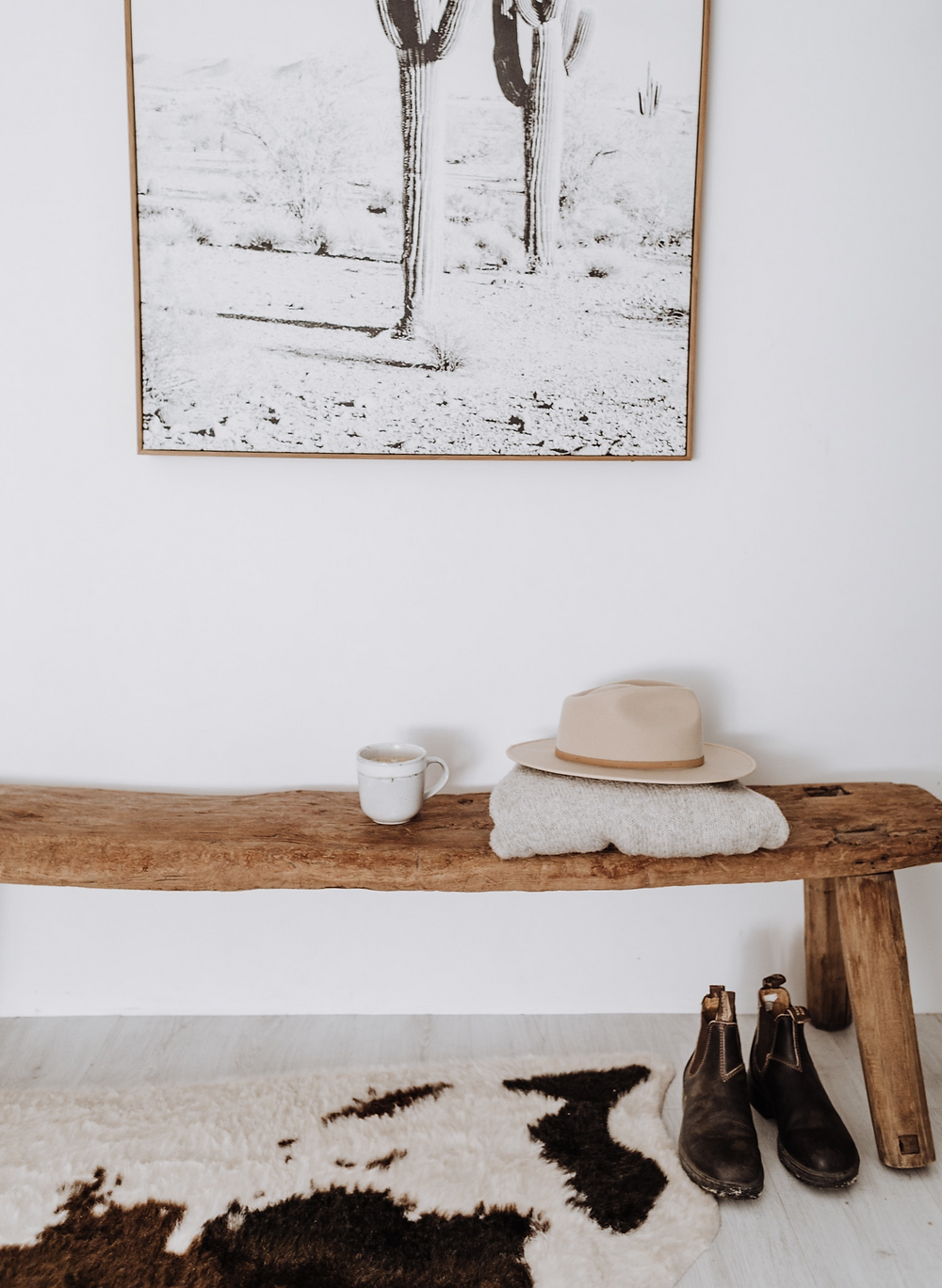 Modern rustic boho neutral home with white walls and raw wooden bench.