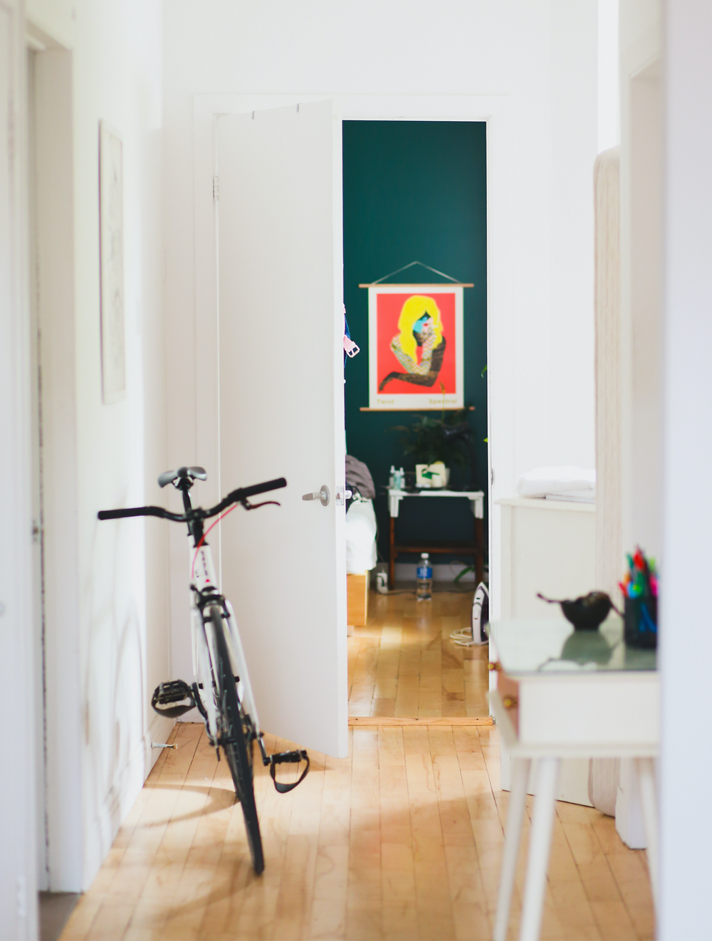 Long apartment hallway with bike and a bold piece of art and deep blue green accent wall at end.