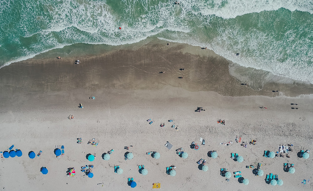 Beautiful seafood green waters on a beach speckled with colorful umbrellas.