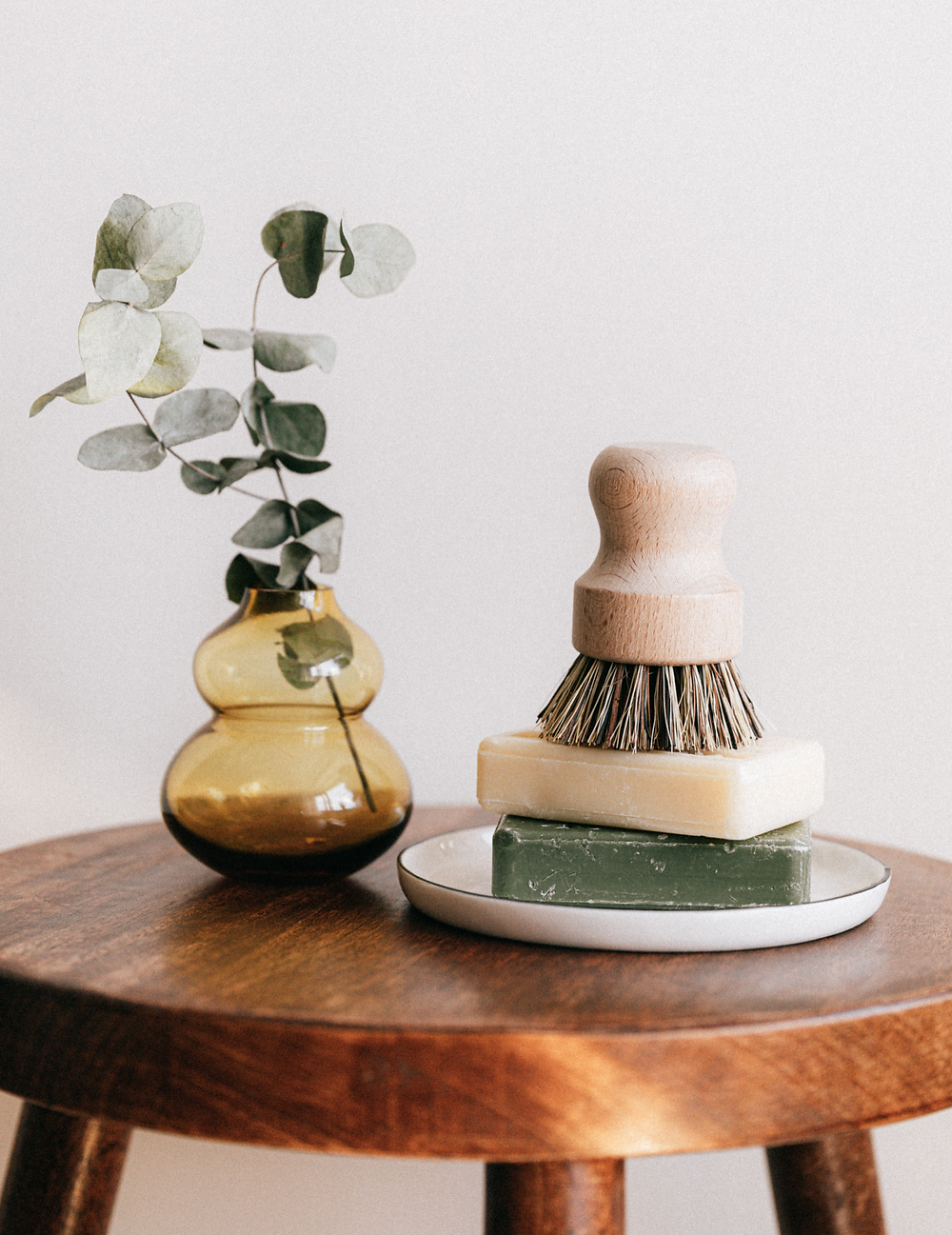 Modern eco friendly and sustainable cleaning with retro amber glass vase and eucalyptus.