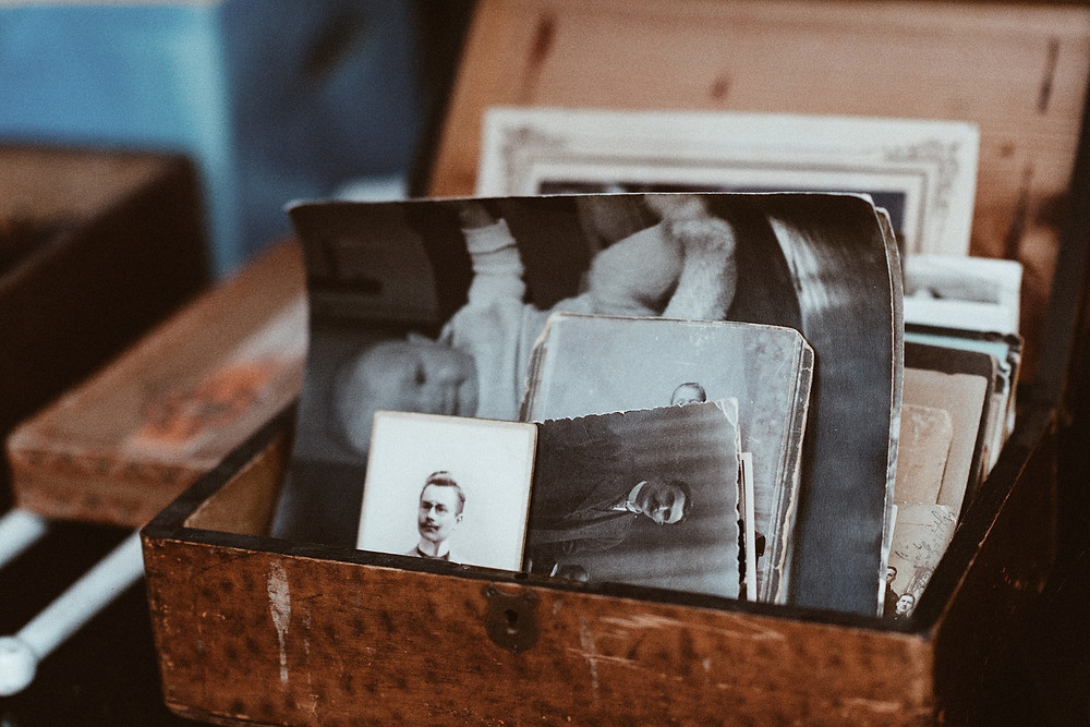 Vintage wooden box with old black and white family photos.