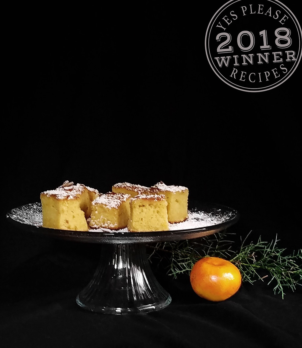An orange Almond Olive Oil Cake with powdered sugar sprinkled on top.
