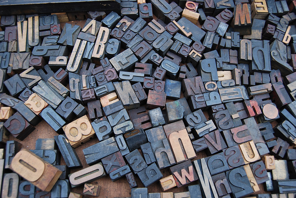 Drawer full of various vintage metal letterpress type press blocks.