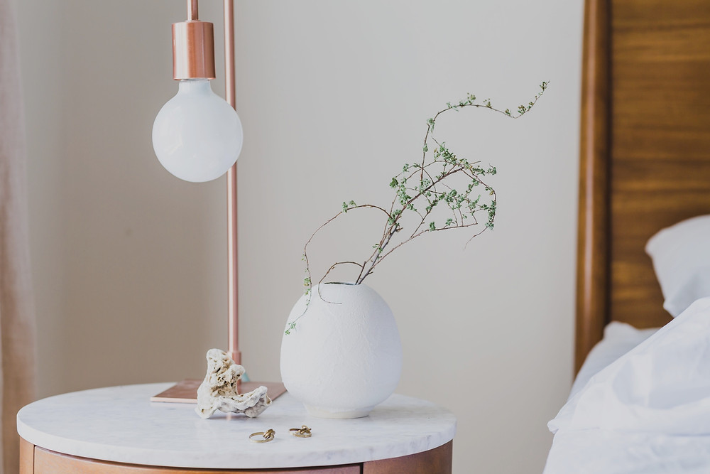 Marble top nightstand with modern bulb lamp and vase with greenery.