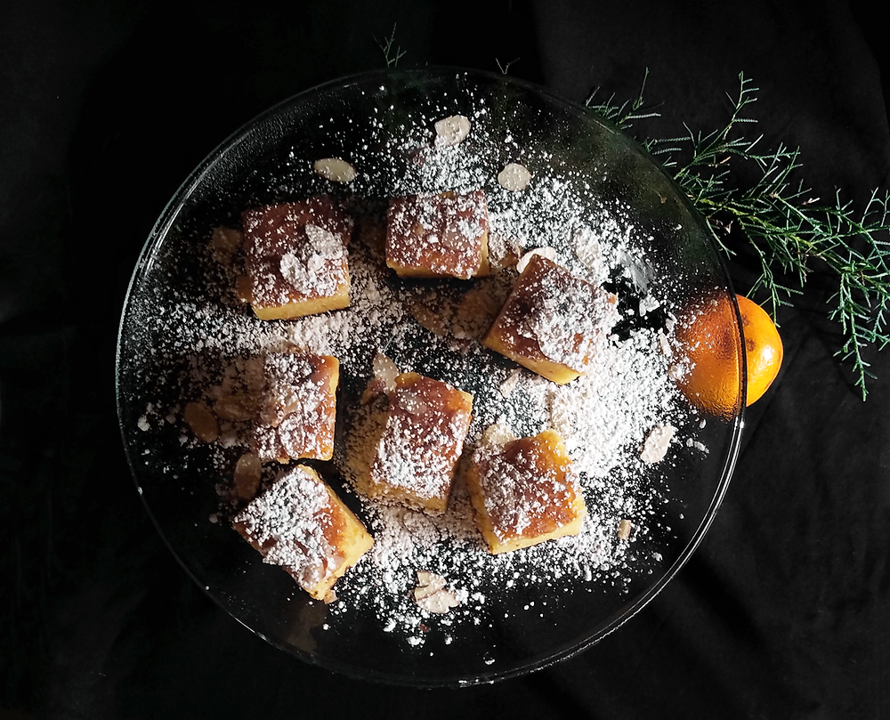 Sliced almonds and powdered sugar on top of orange almond olive oil cake.