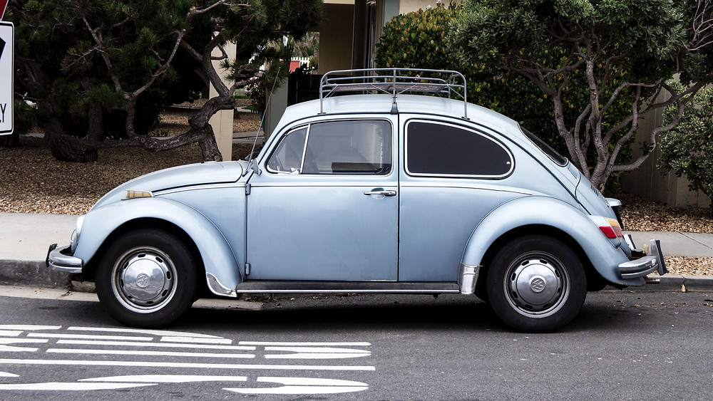 Vintage baby blue VW Bug with luggage rack on top parked on the side of the road.