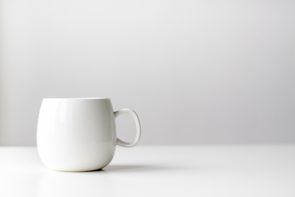 Clean white coffee mug with white background, minimalist photography and design.