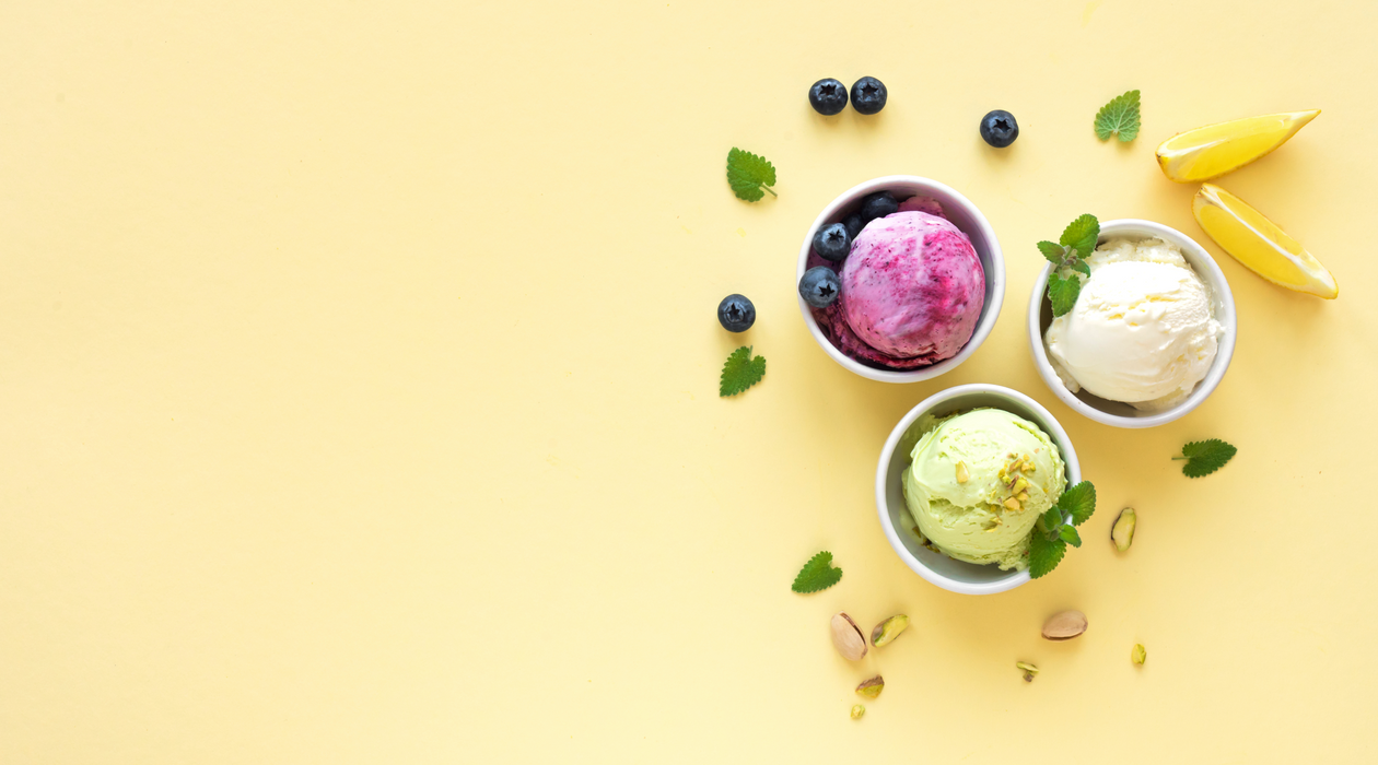 Ice Cream Assortment. Various fruit and berries ice creams on yellow background, copy spac