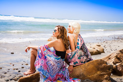 two women sitting on sand