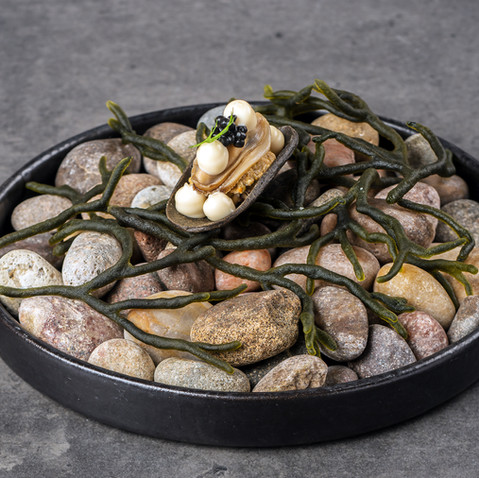 A seaweed poached Shetland mussel with taramasalata, seaweed emulsion, sea purslane and caviar in an edible mussel shell on a bed of pebbles and seaweed.