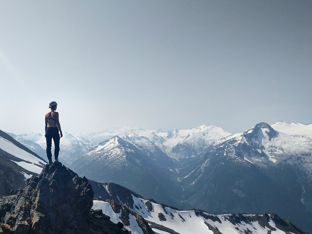 canadian Girl stands on top of a mountain peak staring off into a valley of mountainous snowy ridges