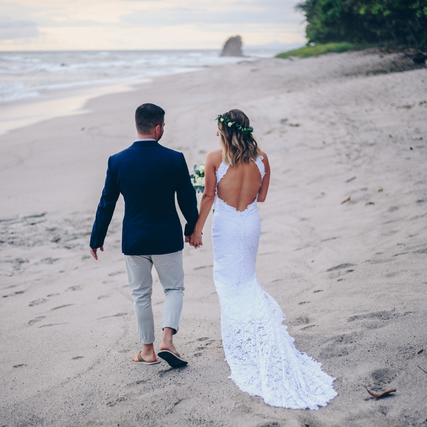 "alt = ""bride n groom walking beach"""