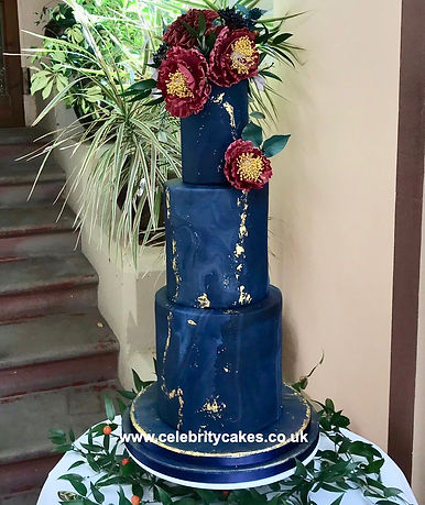 Dark Blue and gold wedding cake with sugar flowers made by Celebrity Cakes Ltd.
