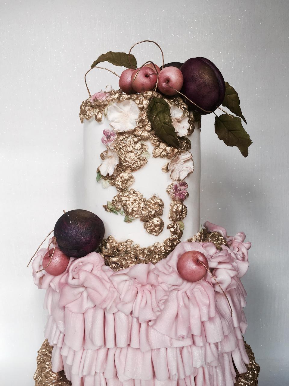Pink ornate ruffle cake with sugar cherr