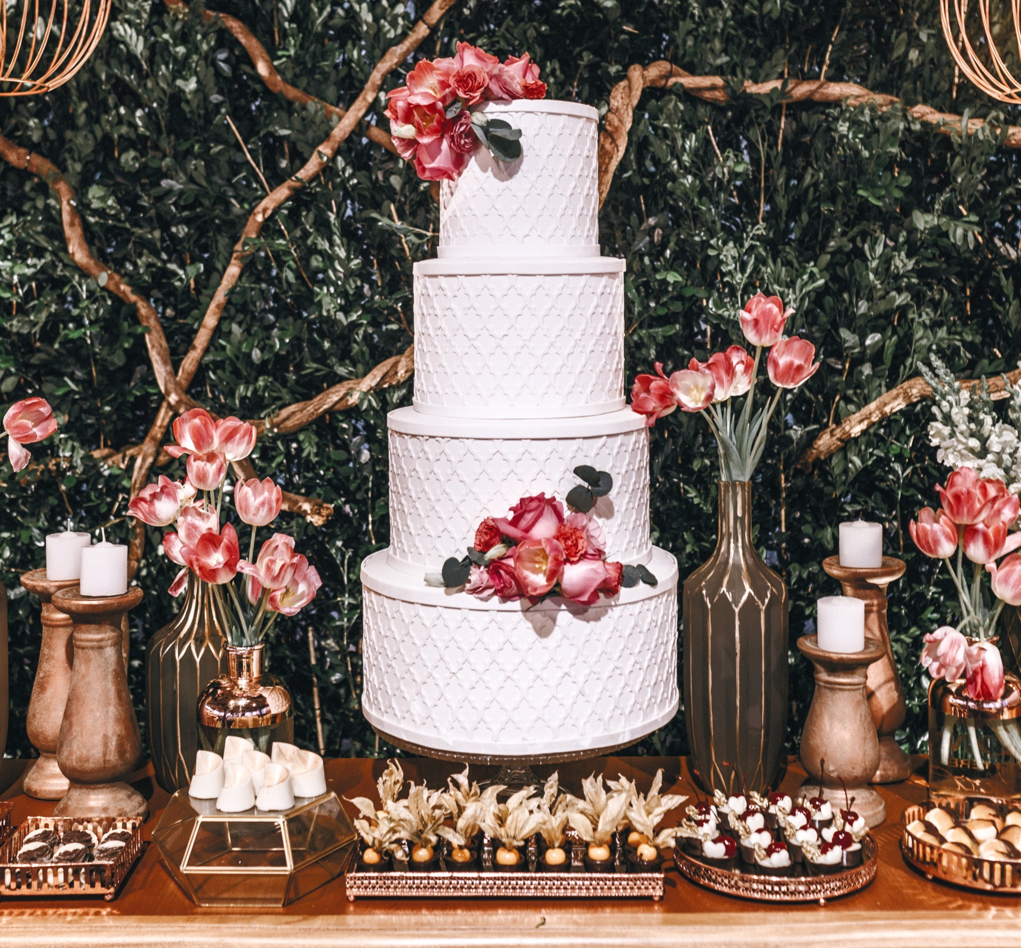 Four tier wedding cake with dessert table