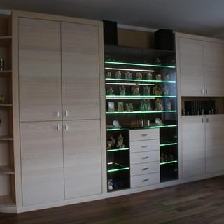Wohnzimmerschrank aus Esche. in der Mitte eine Vitrine mit beleuchteten Glas-Fächer