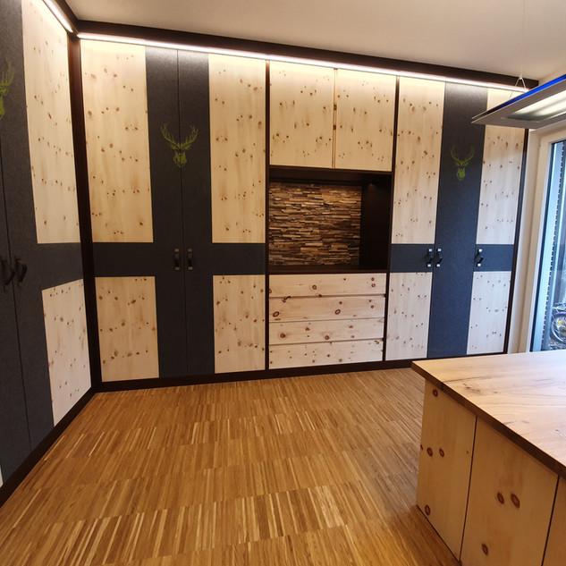 Zirbenholz Wohnzimmer kombiniert mit dunkel gebeizter Buche - sowie Loden-Stoff eingelassen mit Hirschkopf Bestickung mit