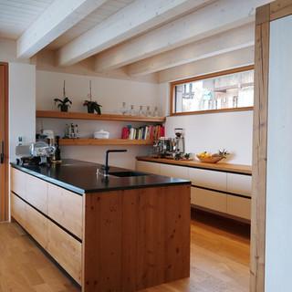 Alholzküche kombiniert mit weiß Holzstruktur eingefräste Griffe mit Metall schwarz hinterlegt