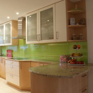 Küche nach Maß mit Granit, weiß, Ahorn, Glasfüllung und grün lackierter Rückwand