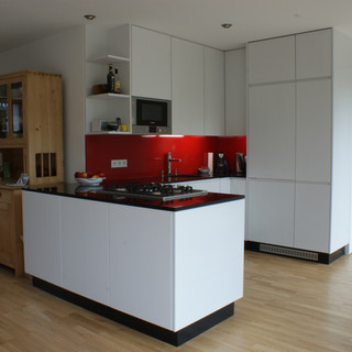 Einbauküche weiß mit Insel und rot lackierter Glas-Rückwand