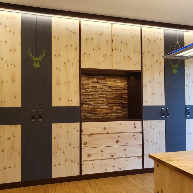 Zirben Wohnzimmerschrank mit Loden-Stoff kombiniert, offener Bereich mit Baumkanten Wand