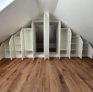Dachschrägen Einbauschrank geöffnet mit Durchgang zu einer Kammer.