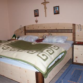 Bett aus Zirbenkiefer kombinert mit Nußbaum - mit geschwungenem Kopfteil